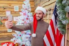Ο τύπος κάνει selfie με μια κινηματογράφηση σε πρώτο πλάνο αμερικανικών σημαιών ενάντια στο σκηνικό ενός διακοσμημένου χριστουγεν Στοκ Εικόνες
