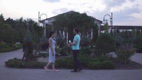 Ο τύπος και ένα κορίτσι συναντιούνται στον κήπο απόθεμα βίντεο