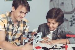 Ο τύπος και το αγόρι κάθονται στον πίνακα Ο τύπος παρουσιάζει στο αγόρι πώς το ρομπότ τακτοποιείται Στοκ Εικόνες