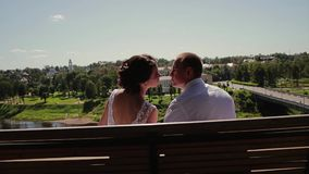 Ο τύπος και το κορίτσι εραστών φιλούν ήπια στα χείλια καθμένος σε έναν πάγκο στις υψηλές όχθεις του ποταμού Πολύ ευγενής και σχετ απόθεμα βίντεο