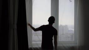 Ο τύπος κλείνει τις κουρτίνες του Tulle στο παράθυρο φιλμ μικρού μήκους