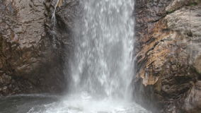 Ο τύπος κολυμπά μέχρι τους υψηλούς Foamy παφλασμούς καταρρακτών μεταξύ των βράχων απόθεμα βίντεο