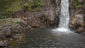 Ο τύπος κολυμπά μέχρι τους υψηλούς Foamy παφλασμούς καταρρακτών μεταξύ των βράχων φιλμ μικρού μήκους