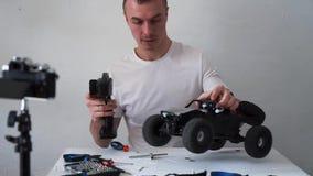 Ο τύπος κρατά έναν τηλεοπτικό blog για τα ραδιο ελεγχόμενα πρότυπα αυτοκινήτων Στον πίνακα είναι εργαλεία για την επισκευή απόθεμα βίντεο