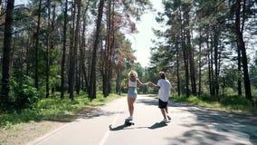 Ο τύπος κρατά το χέρι του κοριτσιού όταν οδηγά skateboard απόθεμα βίντεο