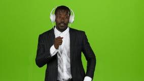 Ο τύπος μαύρων Αφρικανών ακούει τη μουσική μέσω των ακουστικών και τραγουδά εμπρός πράσινη οθόνη απόθεμα βίντεο