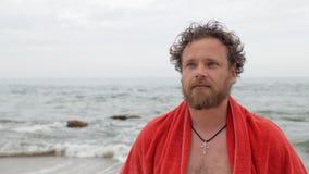 Ο τύπος με μια γενειάδα και τα μπλε μάτια στο υπόβαθρο της θάλασσας με μια πετσέτα στους ώμους του εξετάζει τη κάμερα, γυρίζει το φιλμ μικρού μήκους