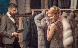 Ο τύπος με τη γενειάδα και η γυναίκα αγοράζουν το γούνινο παλτό στοκ εικόνες