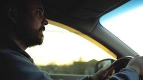 Ο τύπος με τη γενειάδα και mustache οδηγεί ένα αυτοκίνητο στο ηλιοβασίλεμα απόθεμα βίντεο