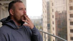 Ο τύπος με τη γενειάδα στέκεται στο μπαλκόνι που καπνίζει ένα τσιγάρο απόθεμα βίντεο