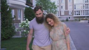 Ο τύπος με τη γενειάδα με τη φίλη του, ένα ξανθό περπάτημα στο πεζοδρόμιο στην πόλη απόθεμα βίντεο