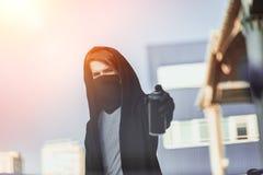 Ο τύπος με τον ψεκασμό μπορεί υπό εξέταση Σχέδιο γκράφιτι Φως του ήλιου στοκ εικόνες