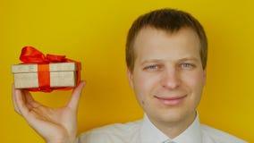 Ο τύπος με το δώρο μέσα στο κιβώτιο χαμογελά και εξετάζει τη κάμερα, στο κίτρινο υπόβαθρο τοίχων φιλμ μικρού μήκους