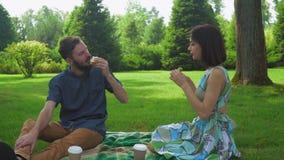 Ο τύπος με το κορίτσι τρώει τα σάντουιτς σαλάτας στο πικ-νίκ που πλένεται κάτω με τον καφέ Επικοινωνήστε ο ένας με τον άλλον φιλμ μικρού μήκους