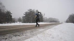 Ο τύπος με το σακίδιο πλάτης τουριστών πηγαίνει μια ομιχλώδη χειμερινή ημέρα Κίνδυνος στο δρόμο το χειμώνα, φιλμ μικρού μήκους