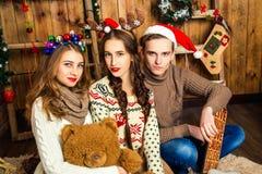 Ο τύπος με δύο κορίτσια σε ένα δωμάτιο με τις διακοσμήσεις Χριστουγέννων Στοκ φωτογραφία με δικαίωμα ελεύθερης χρήσης