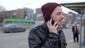 Ο τύπος μιλά στο τηλέφωνο στη στάση λεωφορείου φιλμ μικρού μήκους