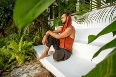 Ο τύπος μόδας κάθεται στους τροπικούς φοίνικες στοκ εικόνες με δικαίωμα ελεύθερης χρήσης