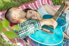 Ο τύπος παίζει την κιθάρα στη φίλη ρομαντική συνεδρίαση ζεύγος θερινών πικ-νίκ που βάζει στη χλόη στοκ εικόνες με δικαίωμα ελεύθερης χρήσης