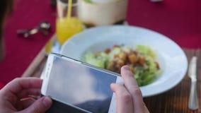 Ο τύπος παίρνει μια εικόνα ενός πιάτου των τροφίμων Πάρτε ένα στιγμιότυπο με ένα γεύμα στο εστιατόριο με μια κινητή τηλεφωνική κά φιλμ μικρού μήκους