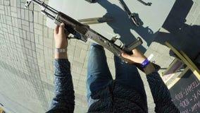 Ο τύπος παίρνει Submachine το πυροβόλο όπλο από τον πίνακα αποσυνθέτει τη τοπ άποψη φιλμ μικρού μήκους