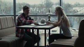 Ο τύπος παρουσιάζει κάτι στο touchpad στο κορίτσι στον καφέ φιλμ μικρού μήκους