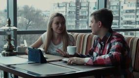 Ο τύπος παρουσιάζει κάτι στο touchpad στο κορίτσι στον καφέ απόθεμα βίντεο