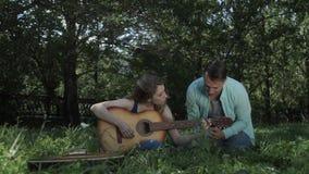 Ο τύπος παρουσιάζει το κορίτσι πώς να παίξει την κιθάρα απόθεμα βίντεο