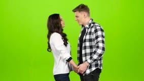 Ο τύπος περιμένει τη φίλη του που έρχεται και τον φιλά ήπια πράσινη οθόνη απόθεμα βίντεο