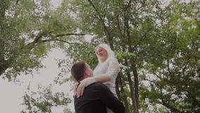 Ο τύπος περιστρέφει τη φίλη του στα όπλα του στο πάρκο Καλά διάθεση και γέλιο απόθεμα βίντεο