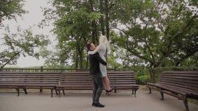 Ο τύπος περιστρέφει τη φίλη του στα όπλα του στο πάρκο Καλά διάθεση και γέλιο φιλμ μικρού μήκους