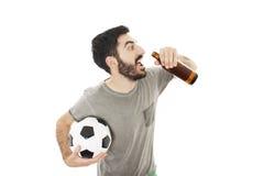 Ο τύπος που κρατά μια σφαίρα ποδοσφαίρου, πίνει την μπύρα Στοκ Φωτογραφίες