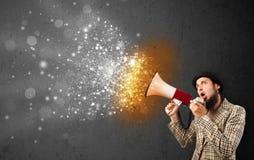 Ο τύπος που φωνάζουν megaphone και τα καμμένος ενεργειακά μόρια εκρήγνυνται Στοκ Φωτογραφία