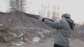 Ο τύπος πυροβολεί ένα πυροβόλο όπλο στη σειρά πυροβολισμού και μετά από τον πυροβολισμό διαστρεβλώνει το παραθυρόφυλλο απόθεμα βίντεο