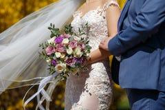 Ο τύπος σε ένα μπλε κοστούμι και ένα κορίτσι σε ένα λευκό αυξήθηκαν lase γαμήλιο φόρεμα με μια ανθοδέσμη των ιωδών λουλουδιών και στοκ φωτογραφίες