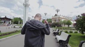 Ο τύπος σηκώνεται από τον πάγκο στο πάρκο και γρήγορα τα φύλλα απόθεμα βίντεο
