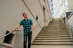 Ο τύπος στέκεται στα σκαλοπάτια και σκέφτεται για την επιτυχία στοκ εικόνα