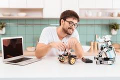 Ο τύπος στα γυαλιά είναι απασχολημένος με το ρομπότ Διευθύνει τις μετρήσεις των κυκλωμάτων ρομπότ χρησιμοποιώντας ένα πολύμετρο Στοκ Φωτογραφίες