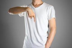 Ο τύπος στην άσπρη μπλούζα που δείχνει το δάχτυλο κάτω Διευκρινίζει το dir Στοκ φωτογραφία με δικαίωμα ελεύθερης χρήσης