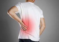 Ο τύπος στην άσπρη μπλούζα προσκολλάται στην πλάτη του Πόνος στο χαμηλότερο β στοκ φωτογραφία με δικαίωμα ελεύθερης χρήσης