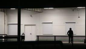 Ο τύπος στην κουκούλα στέκεται τη νύχτα κοντά στον τοίχο απόθεμα βίντεο