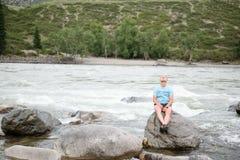 Ο τύπος στην όχθη ποταμού κάθεται σε έναν βράχο στοκ εικόνες