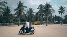 Ο τύπος στη μοτοσικλέτα οδηγά μακριά τις παραμονές κοριτσιών στο τετράγωνο χώρων στάθμευσης απόθεμα βίντεο