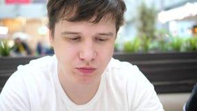 Ο τύπος στο εστιατόριο γρήγορου φαγητού τρώει τις τηγανισμένες πατάτες σε ένα πιάτο Κινηματογράφηση σε πρώτο πλάνο προσώπου Φέτες φιλμ μικρού μήκους