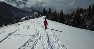 Ο τύπος στο κοστούμι σκι είναι σε ένα χιονώδες ίχνος στα βουνά επάνω από τα σύννεφα απόθεμα βίντεο