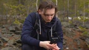 Ο τύπος-τουρίστας σπρώχνει το δάχτυλό του στο κινητό τηλέφωνο απόθεμα βίντεο