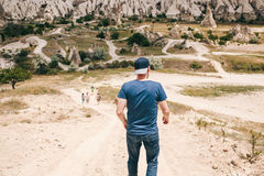 Ο τύπος τουριστών προσπαθεί να προφθάσει τους φίλους τουριστών του στο δρόμο στη λοφώδη επαρχία Cappadocia μέσα Στοκ Εικόνα