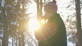 Ο τύπος το χειμώνα ντύνει το καυτό θερμαμένο κρασί κατανάλωσης στο ηλιοβασίλεμα στο χειμερινό δάσος, χειμερινή διασκέδαση, αργό M φιλμ μικρού μήκους