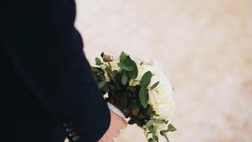 Ο τύπος φέρνει στο χέρι του μια όμορφη ανθοδέσμη των λουλουδιών o r Θαυμάσιοι cinematic πυροβολισμοί απόθεμα βίντεο