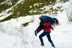 Ο τύπος φέρνει τη φίλη του στον ώμο του στο χειμερινό λιβάδι στοκ εικόνες
